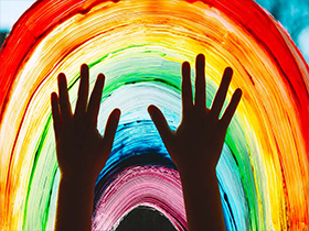 Hands painting rainbow